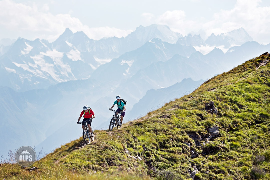 Two mountain bikers riding singletrack with the Alps in the background during the Swiss CrissCross project. Road ride through the Alps across Switzerland, then mountain bike back through the Alps on trails. 2012