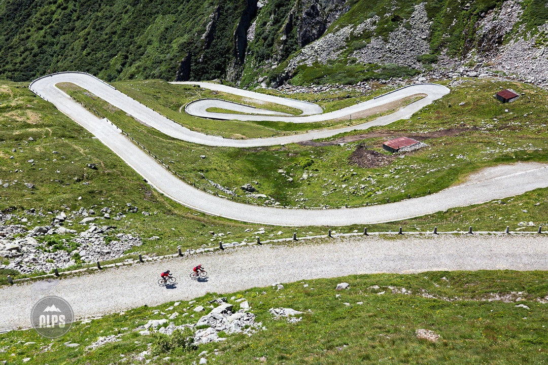 Two road bikers descending the cobblestone road of the Gotthard Pass on day 3 of the Swiss CrissCross project. Road ride through the Alps across Switzerland, then mountain bike back through the Alps on trails. 2012