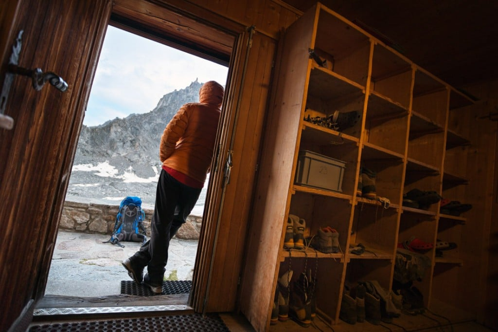 A hiker stands in the entrance to the Cabane d'Orny looking out at the weather on the second day of the Chamonix to Zermatt Glacier Haute Route