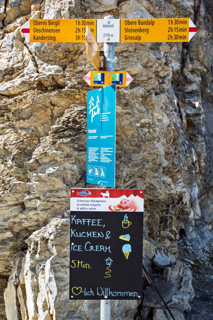 A Swiss wanderweg trail sign with notice of a hut and the menu with ice cream