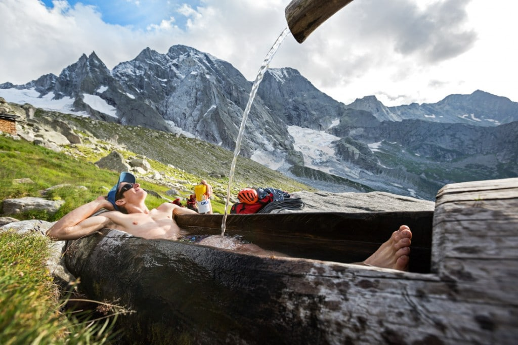 A climber lays in the fountain at the Sciora Hut drinking a beer and laughing. Switzerland