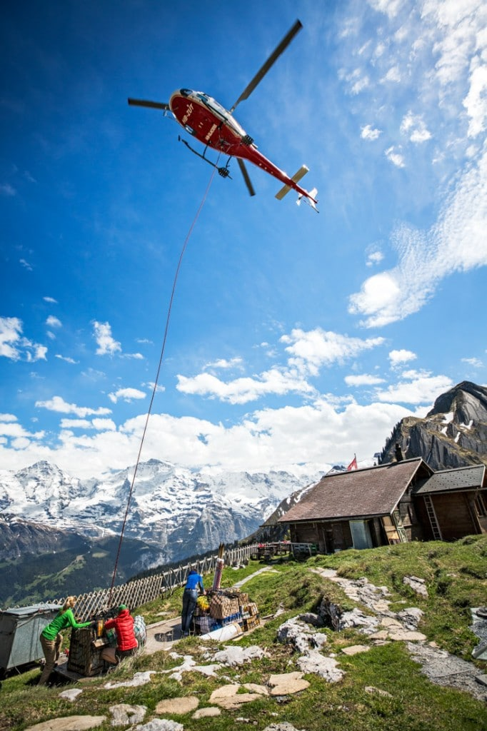 Huts in the Swiss Alps receive their supplies by helicopter transport, here a helicopter drops off food for the Lobhorn Hut, Berner Oberland, Switzerland