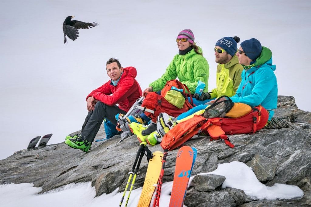 A group of ski tourers sitting on a rock at the Konkordiaplatz taking a break to eat and drink as a black bird flies by, while on a ski tour of the Berner Oberland, Switzerland