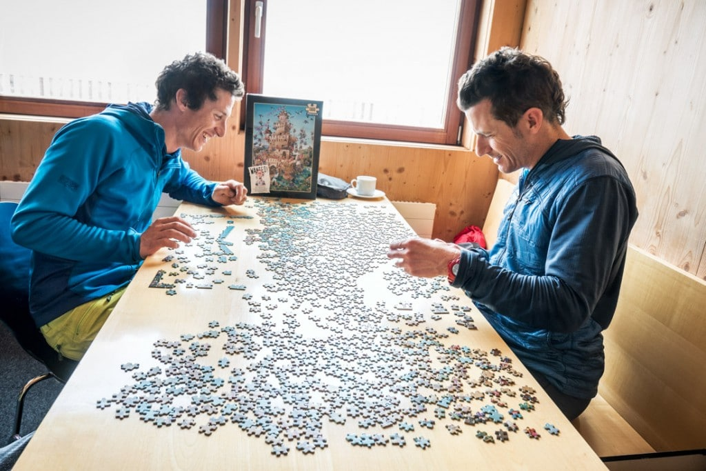 Two men doing a puzzle while in the Finsteraarhorn Hut on a bad weather day during a ski tour of the Berner Oberland, Switzerland.