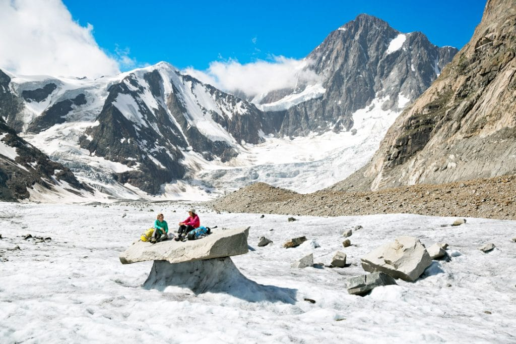 Two female hikers sitting on a large granite boulder on the Finsteraargletscher taking a break from trekking to eat and drink