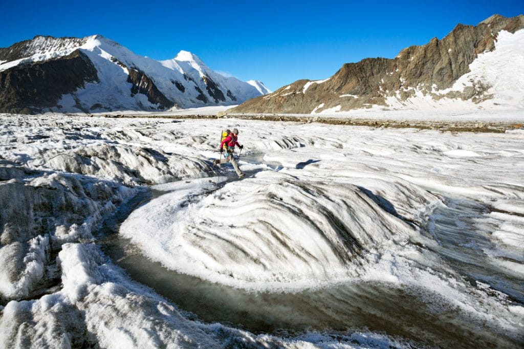 A hiker on the Aletschgletscher crosses a water channel in the ice. The Aletsch is Europe's largest glacier at nearly 24km in length.