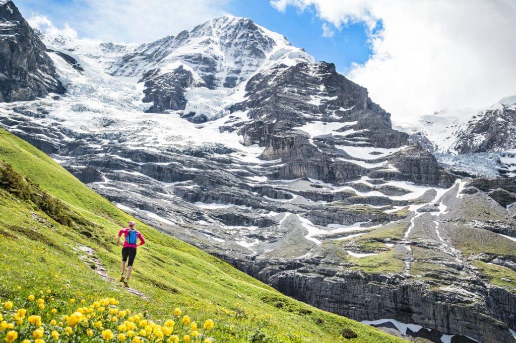 A woman trail runner on mountain trails from Lauterbrunnen to Kleine Scheidegg, in the Berner Oberland region of Switzerland