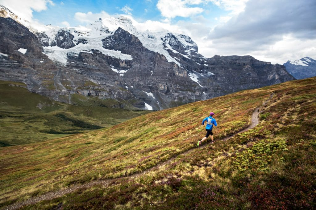 A woman trail running around Kleine Scheidegg in fall colors, Switzerland. The Jungfrau Group is in the background, the Eiger, Mönch and Jungfrau.