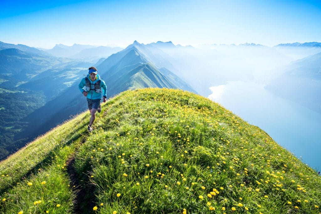 Trail running on the Hardergrat on a sunny, summer day. The green, grassy ridge connects Interlaken with Brienz, Switzerland with the trail staying right on the crest of the ridge for almost the entire 25km of length.