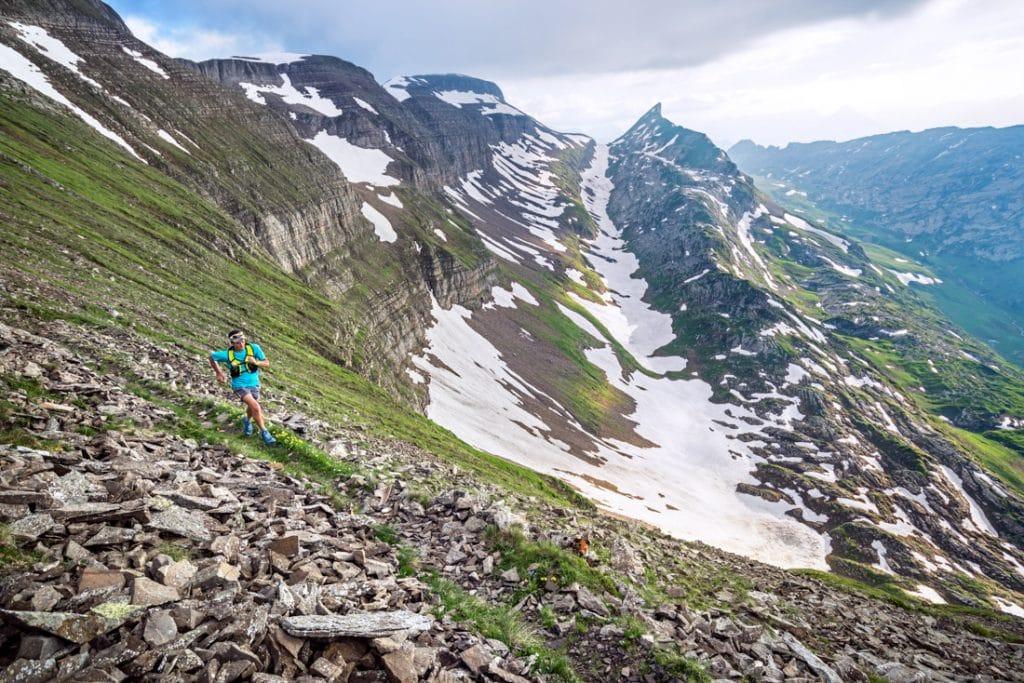 Trail running on a high singletrack trail in rocky terrain with snow still up high, above Interlaken, Switzerland