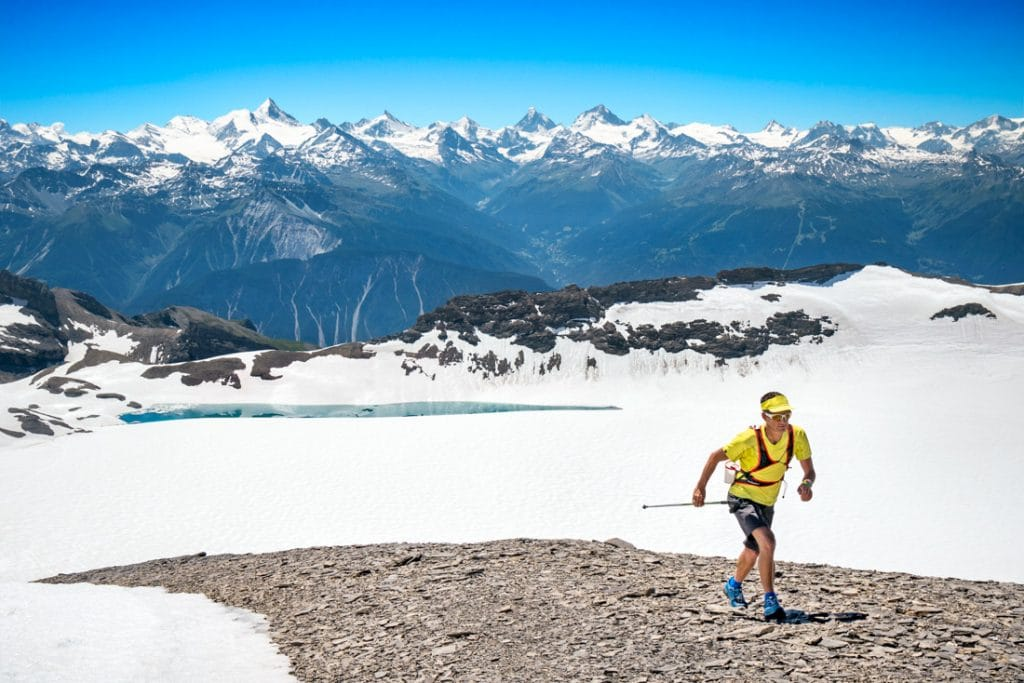 Trail runner arriving to the summit of the Wildstrubel, a 3244 meter peak in the Swiss Alps above Lenk, Switzerland. In the background is the Plaine Morte, a huge flat glacier.