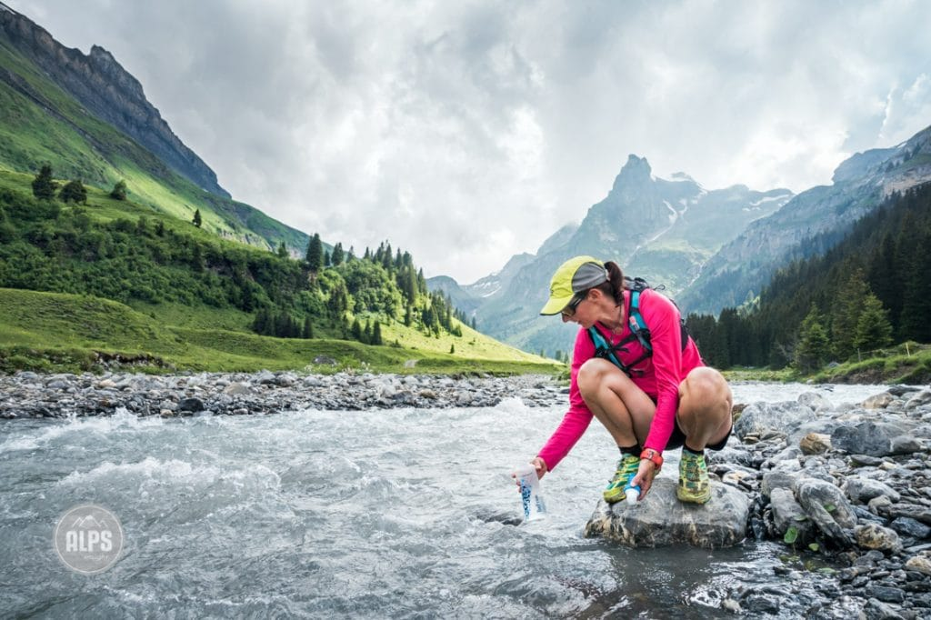 A trail runner stops at a river in the Swiss Alps to fill a Katadyn BeFree water filter