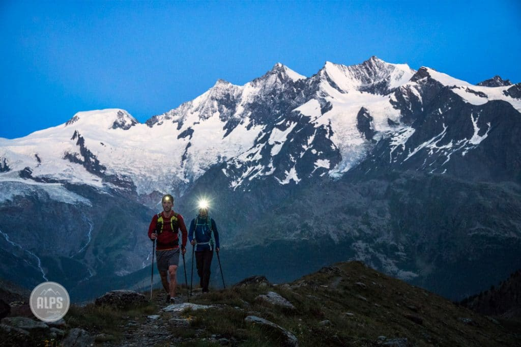 Two people hiking up the Lagginhorn in the pre-dawn darkness, using headlamps. Saas Grund, Switzerland