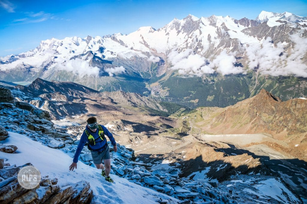 A hiker on the 4010 meter Lagginhorn crosses a snowy section while doing a fast climb of the peak from Saas Grund, Switzerland