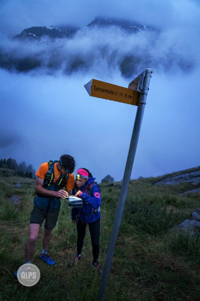 Two runners stopped at a trail sign to look at a map with their headlamps in the pre-dawn light. Turtmenntal, Switzerland