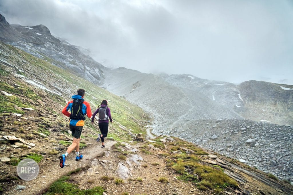 Two trail runners in changing weather climbing the Üssers Barrhorn (3610 meters), the highest peak in Switzerland that has a trail to the top. Turtmenntal, Switzerland