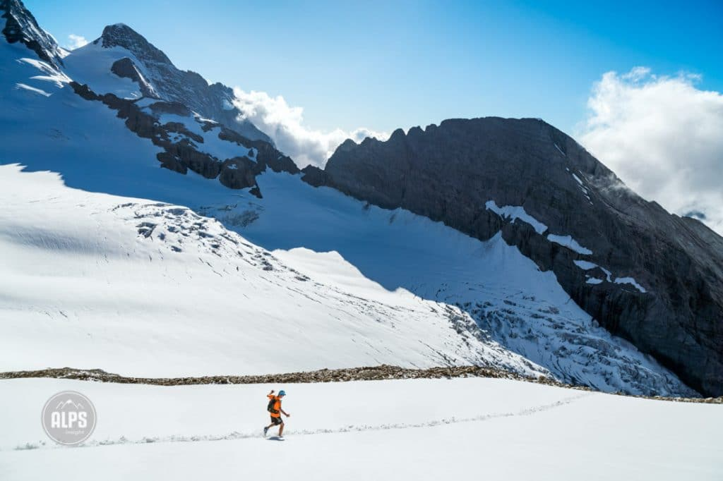 A trail runner descends a snow field off the Dossen Peak, after a 2000 meter ascent from Rosenlaui. Below is the Rosenlauigletscher.