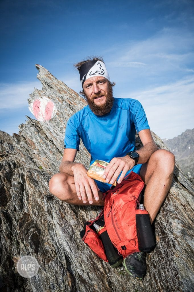 A trail runner stops to eat while on a running tour through Austria