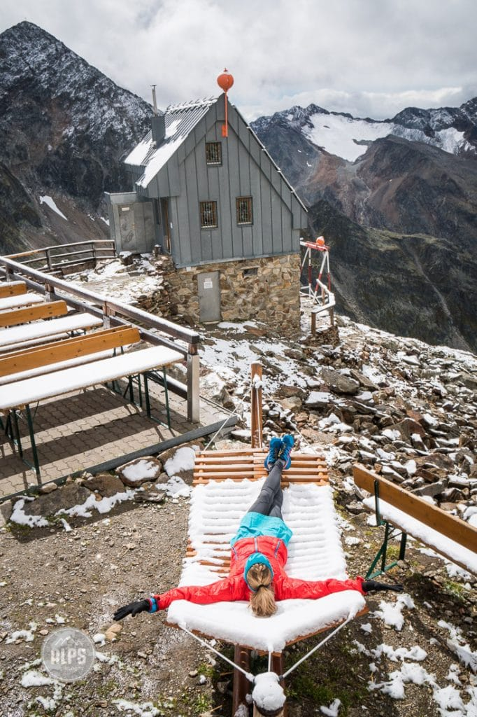 A woman jokingly lays on a snow covered lounge outside a hut during a multi-day running tour through Austria