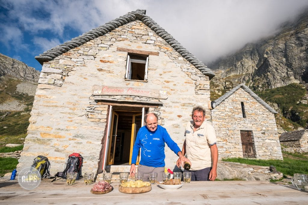 The Via Alta Verzasca is a five day ridge traverse hike above the Valle Verzasca in the Ticino region of Switzerland. Giorgio Matasci, president of the Società Escursionistica Verzaschese, prepares food and drink for hikers at the Capanna Cognora.