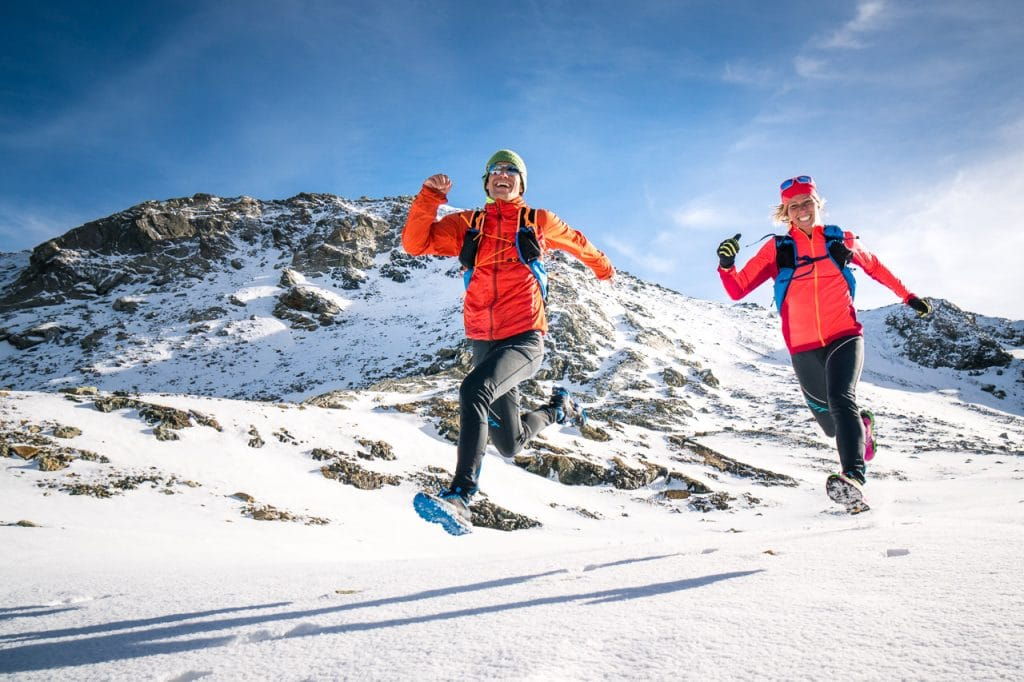 Two runners laughing while running downhill on the Piz Lunghin above Maloja, Switzerland after an early winter snow storm.