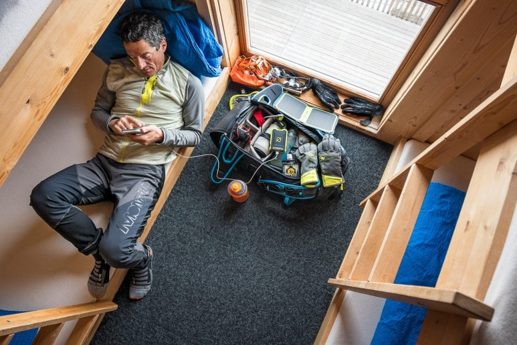 Using a solar panel inside the Finsteraarhorn Hut to charge a phone and camera, during a ski tour of the Berner Oberland, Switzerland.