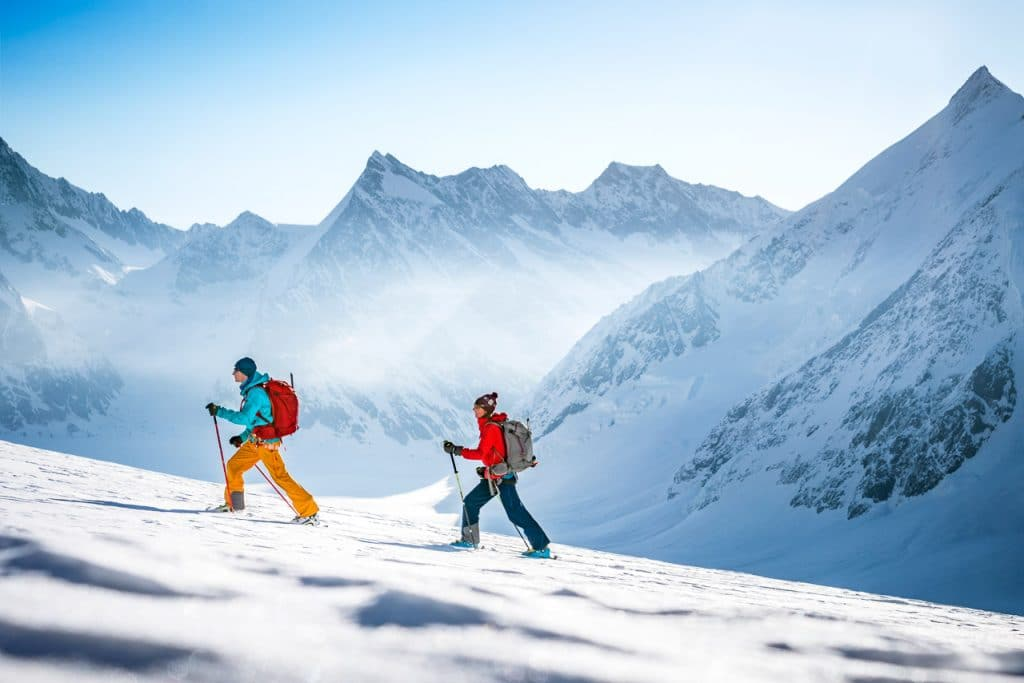 Two ski tourers on their way up the Mittaghorn during a ski tour of the Berner Oberland, Switzerland