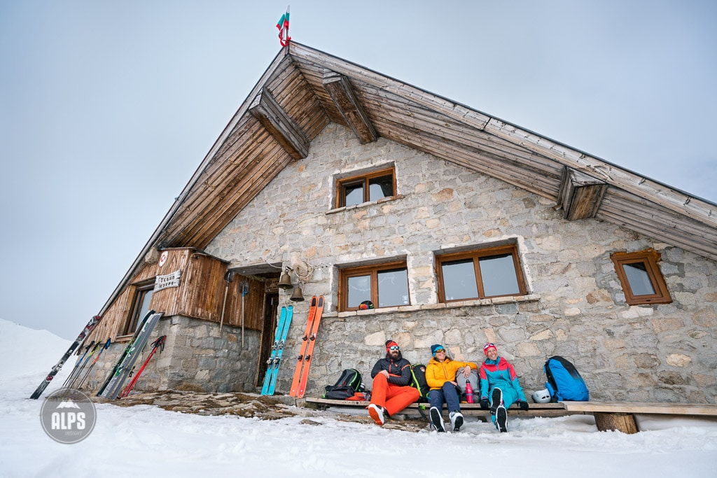 A ski tour through the Pirin Mountains of Bulgaria. Skiers relaxing outside the Tevno Ezero Hut.