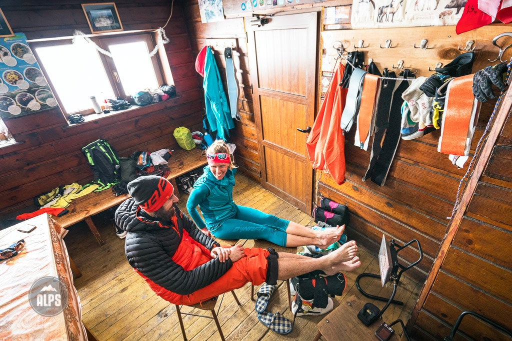 A ski tour through the Pirin Mountains of Bulgaria. Inside the Tevno Ezero Hut a couple dries out their ski gear and warms up next to a heater.