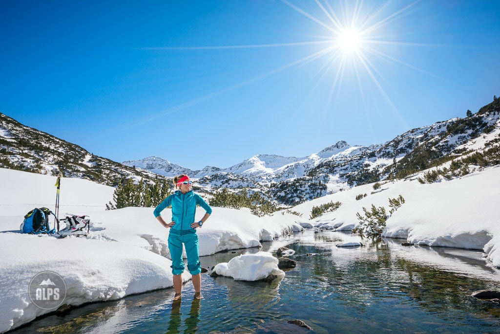 A ski tour through the Pirin Mountains of Bulgaria. A woman stands barefoot in a small creek with her skis next to the water.