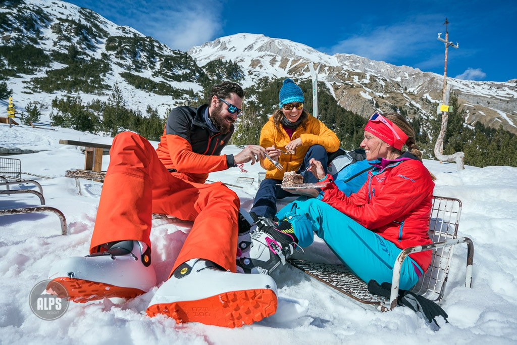A ski tour through the Pirin Mountains of Bulgaria. A group of friends sit at the Vihren Hut eating birthday cake after a successful ski tour through the Pirin Mountains.