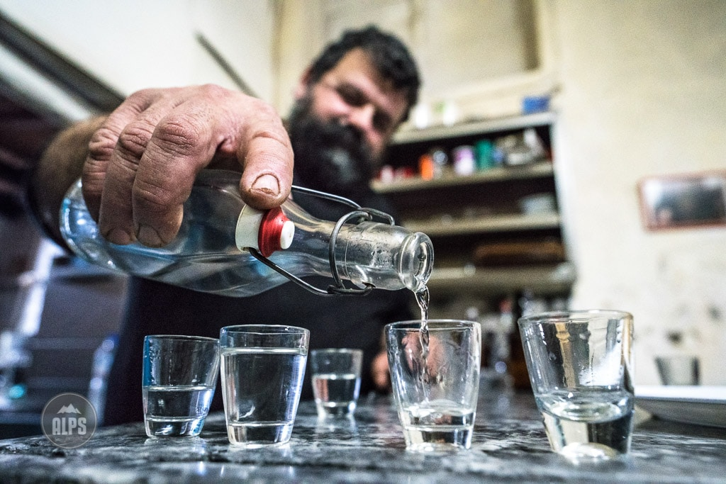 The owner of a Greek restaurant pours raki into small glasses. Crete, Greece.