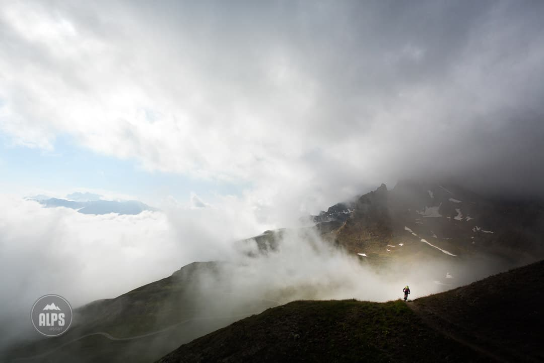 A lone mountain biker amongst clearing clouds above Samnaun while on the Swiss CrissCross project. Road ride through the Alps across Switzerland, then mountain bike back through the Alps on trails. 2012