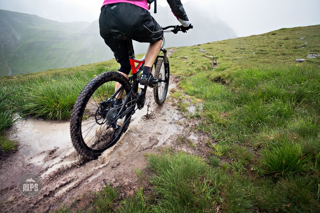 A mountain biker riding through a mud puddle in the rain in the Swiss Alps during the Swiss CrissCross project. Road ride through the Alps across Switzerland, then mountain bike back through the Alps on trails. 2012