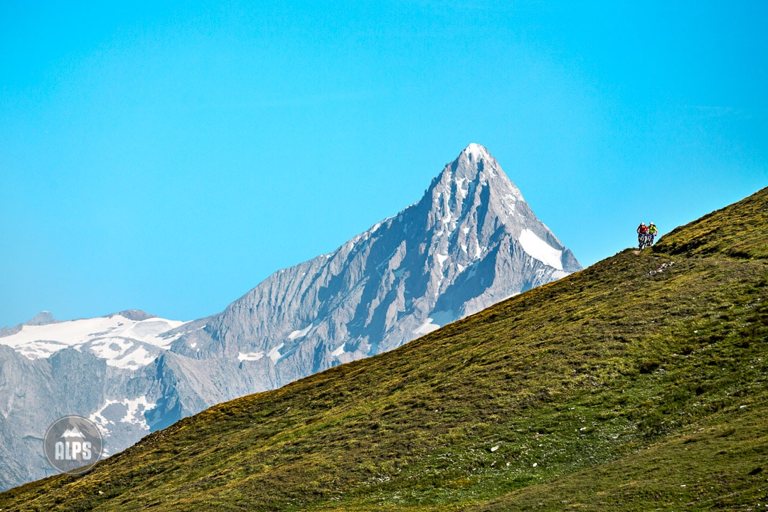 Dramatic photo of two mountain bikers riding singletrack with the Bietschorn in the background during the Swiss CrissCross project. Road ride through the Alps across Switzerland, then mountain bike back through the Alps on trails. 2012