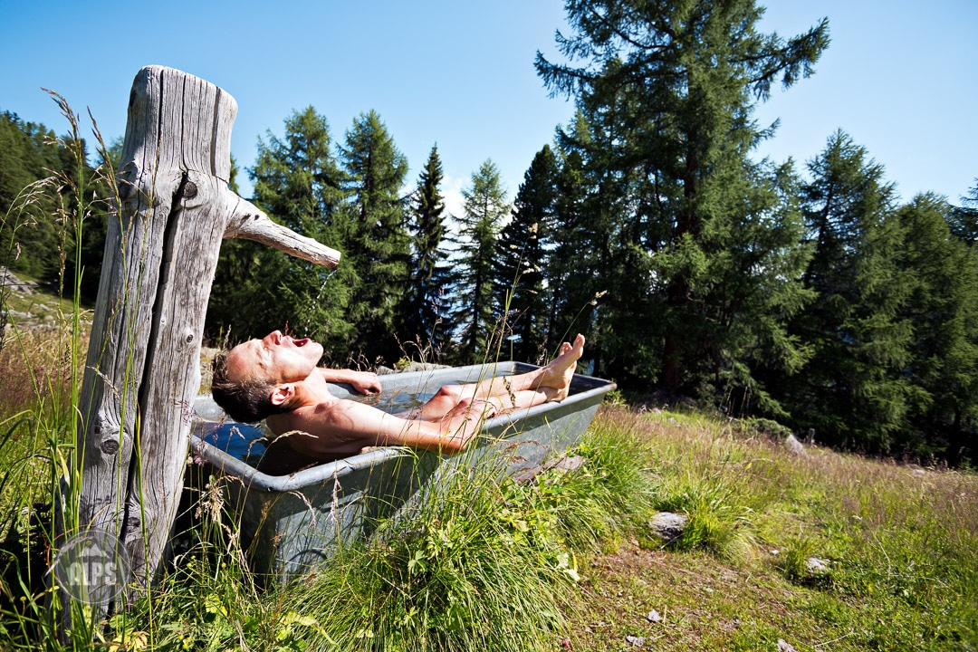 A man sits soaking and relaxing in the cool water of an outdoor bath tub during the Swiss CrissCross project. Road ride through the Alps across Switzerland, then mountain bike back through the Alps on trails. 2012