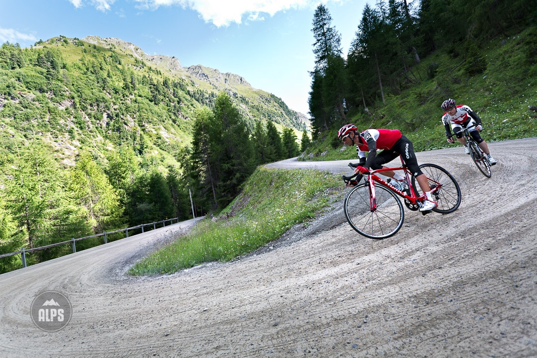 Two road bikers descending the dirt portion of the Umbrail Pass down to Santa Maria from Passo Stelvio on day 5 of the Swiss CrissCross project. Road ride through the Alps across Switzerland, then mountain bike back through the Alps on trails. 2012