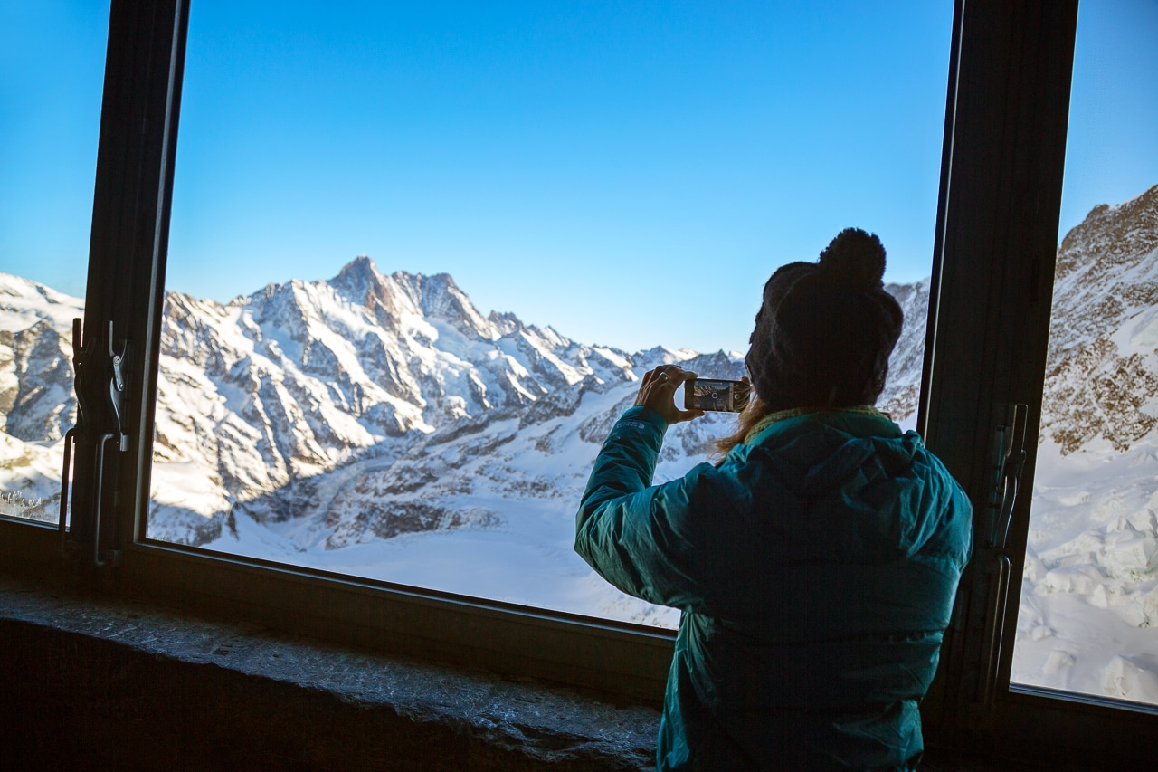 A tourist taking photos from the Jungfraujoch train tunnel where it stops inside the Eiger and has viewing windows