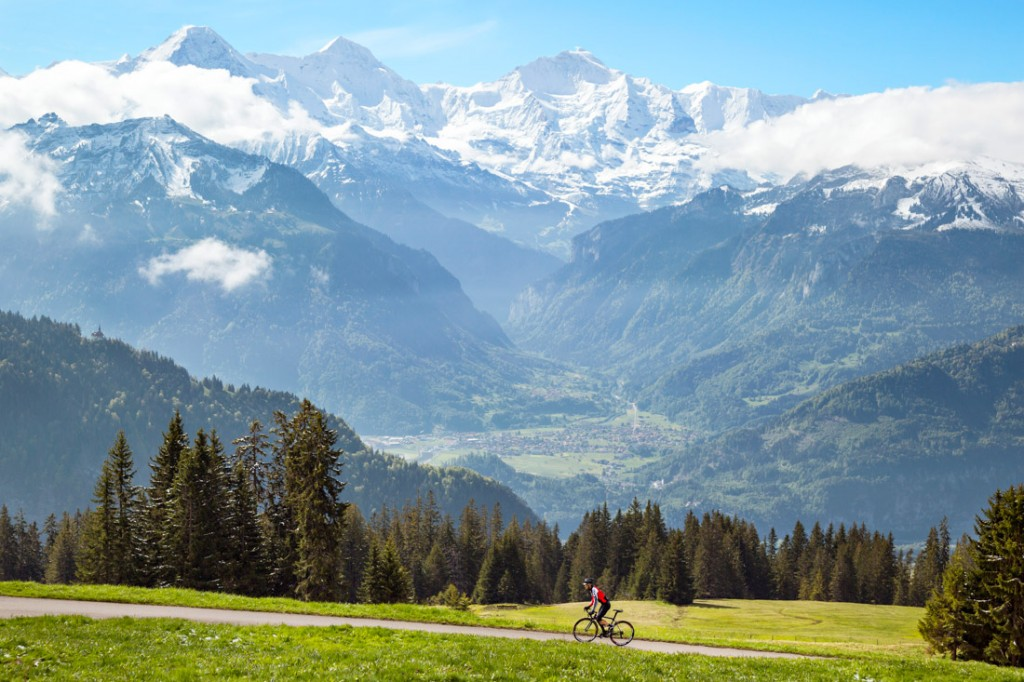 A road biker climbs a small road above Interlaken, Switzerland on a spring morning with views of the Eiger, Mönch and Jungfrau