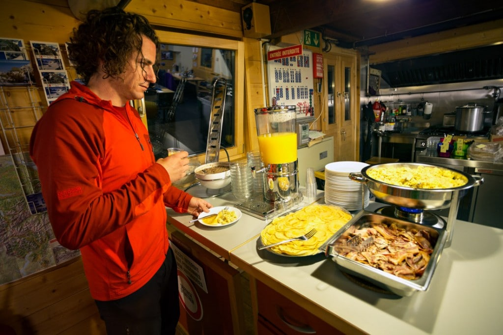 A trekker stands at the breakfast counter at the Vignette Hut during a hike of the Chamonix to Zermatt Glacier Haute Route