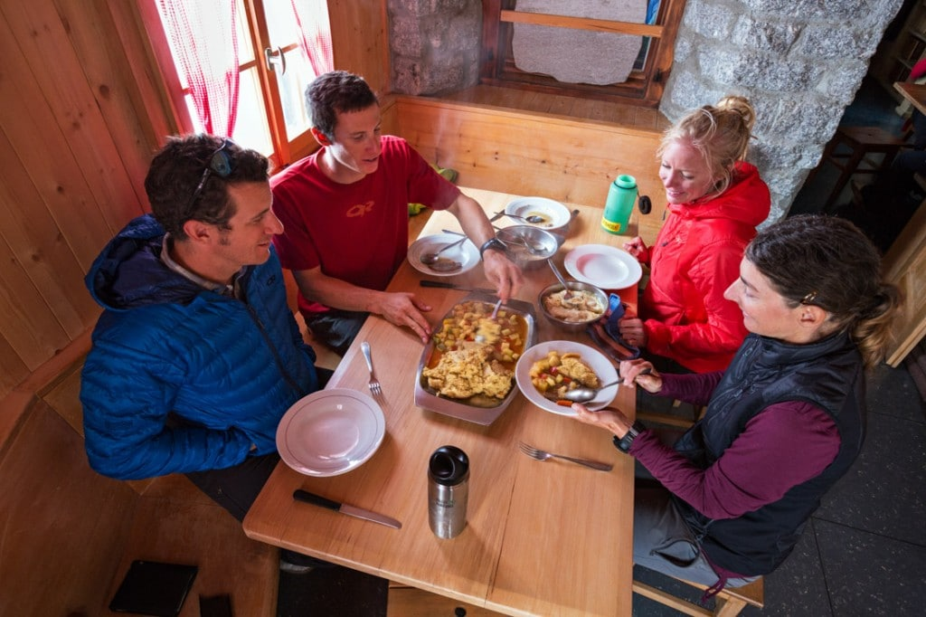 A group of friends having dinner inside the Sciora Hut, Switzerland