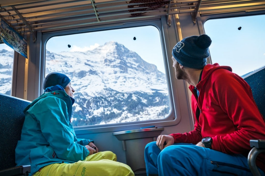 Two skiers on the Jungfraujoch Train headed to Kleine Scheidegg, with the North Wall of the Eiger out the train window, Switzerland