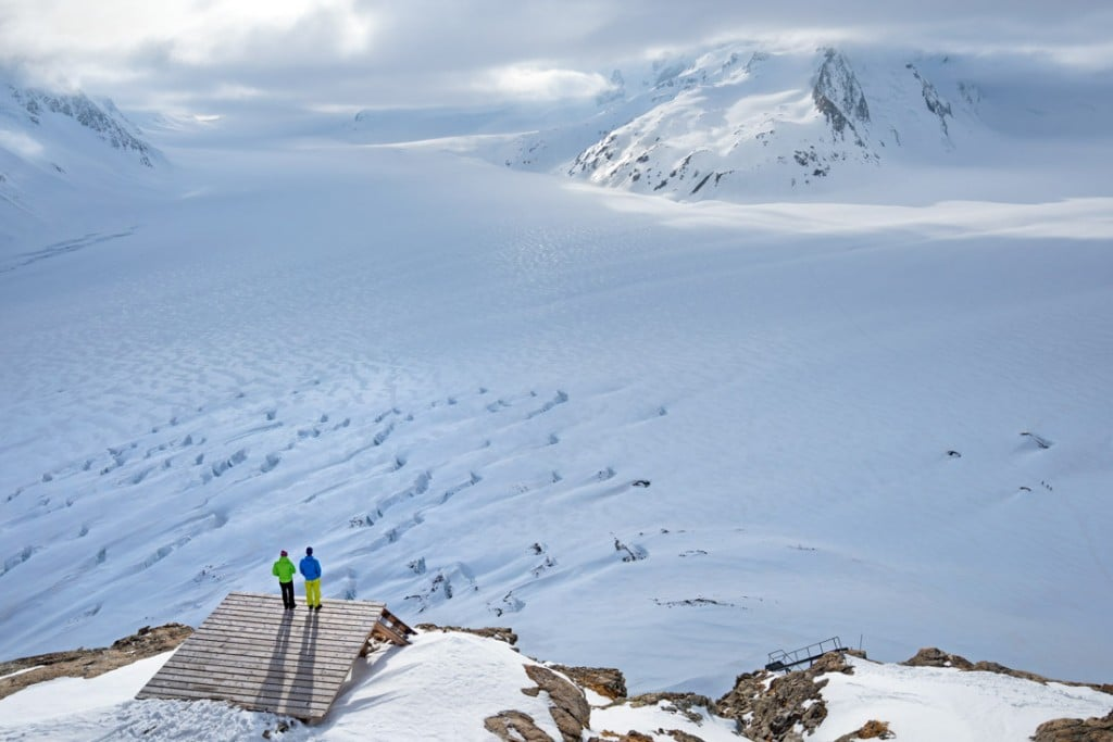 Ski tourers sitting at the Konkordia Hut look out on the massive Konkordiaplatz, part of the Aletschgletscher, the Alps biggest glacier, while on a ski tour of the Berner Oberland, Switzerland