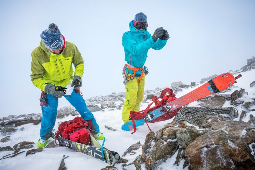 Climbing the Finsteraarhorn with skis in a storm, during a ski tour of the Berner Oberland, Switzerland. The skiers are stopped to put on more clothing and warm up.