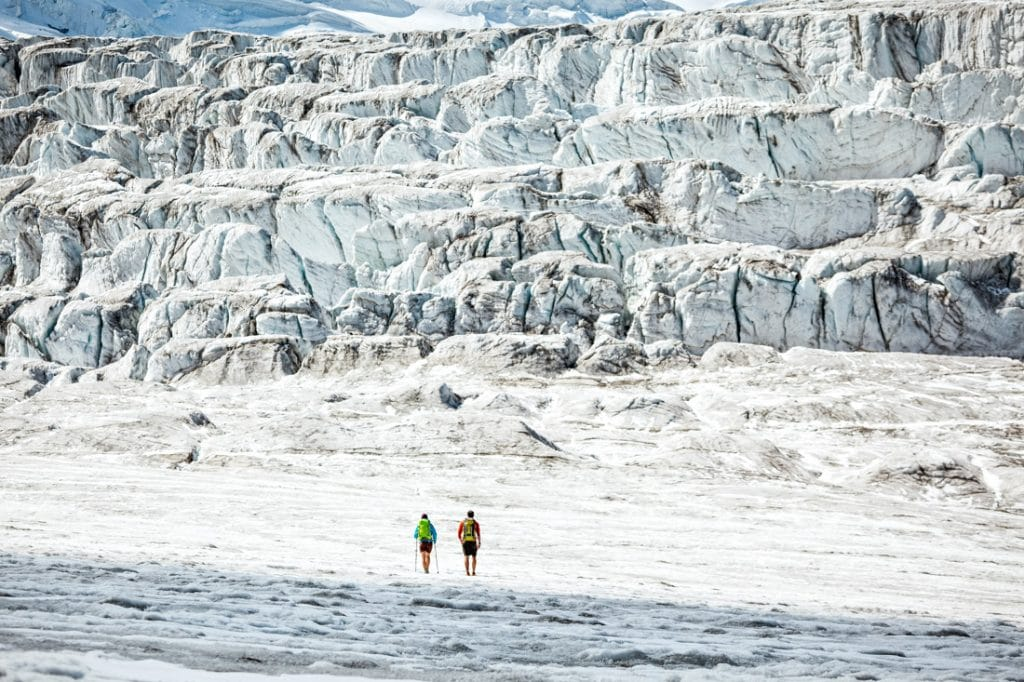 Two hikers on the Glacier de Cobassiere during a hiking tour of the Grand Combin Circuit. They are within an ice fall zone of massive seracs. Switzerland