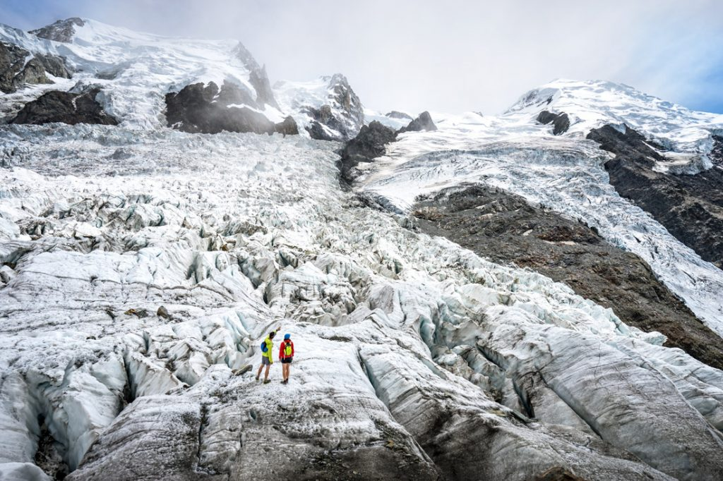 Two hikers standing on the Glacier des Bossons beneath Mont Blanc while hiking in Chamonix, France.