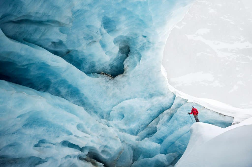 Exploring a glacier's blue ice inside a huge serac on the Glacier de Zinal while on a backcountry ski tour. Switzerland