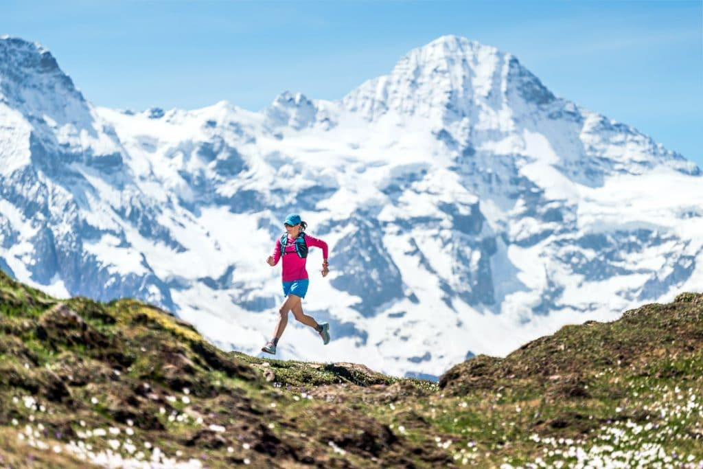 A woman trail running above Grindelwald, Switzerland with views of the Jungfrau