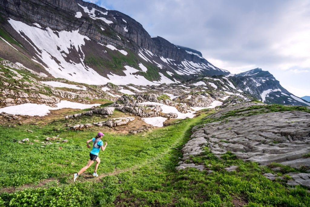 Trail running on a green, grassy singletrack trail above Interlaken, Switzerland