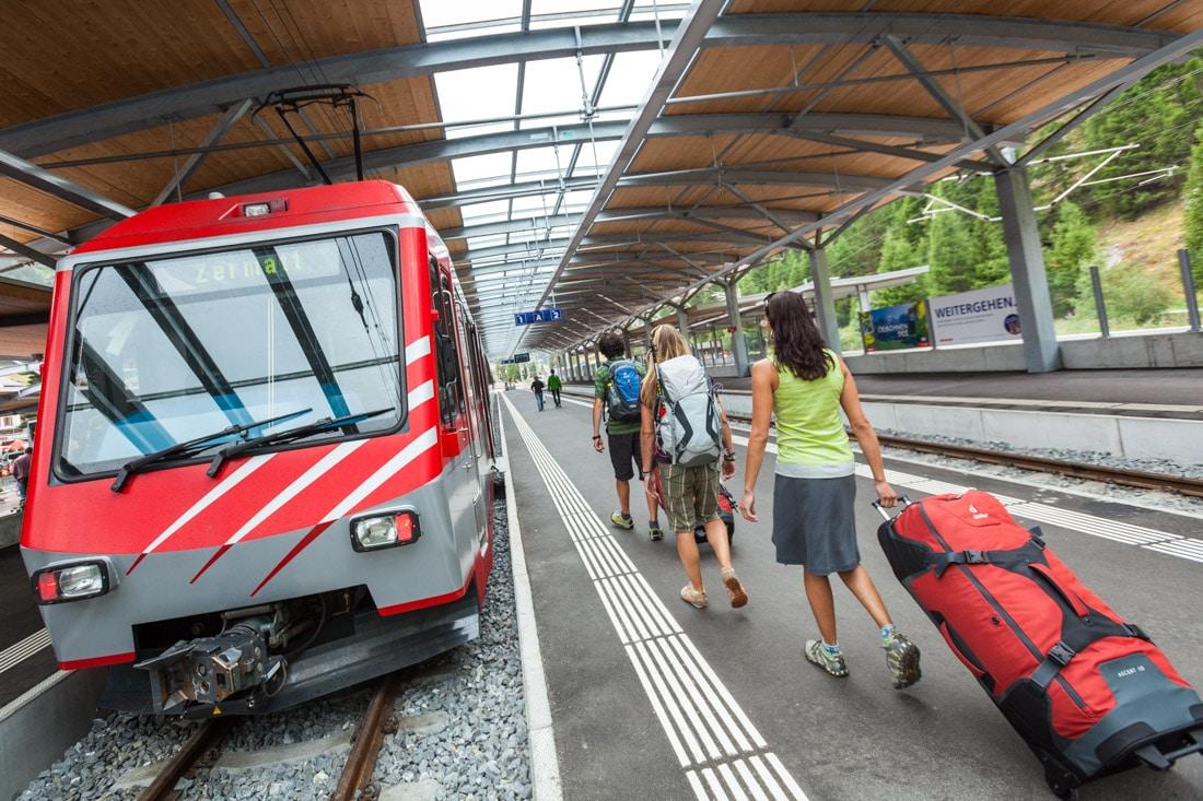 Travelers using Swiss trains for getting around Switzerland. The Zermatt train station.